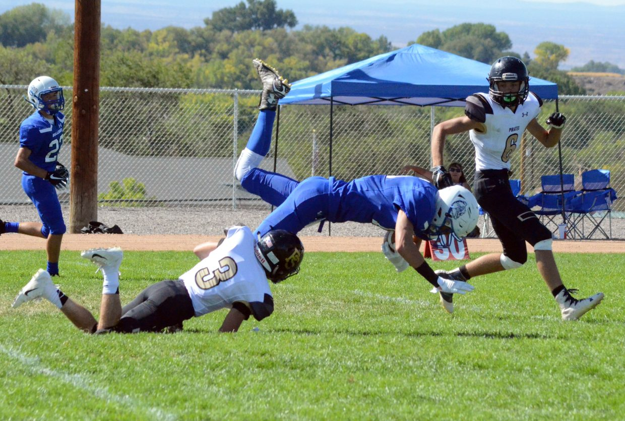 Moffat County High School's Kameron Baker is tripped up but stretches for the first down.