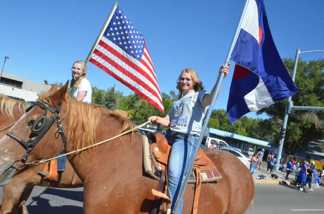 Moffat County High School FFA members Brianna Burkett and Alexis Blomquist carry the American and Colorado flags during Friday's Homecoming parade.