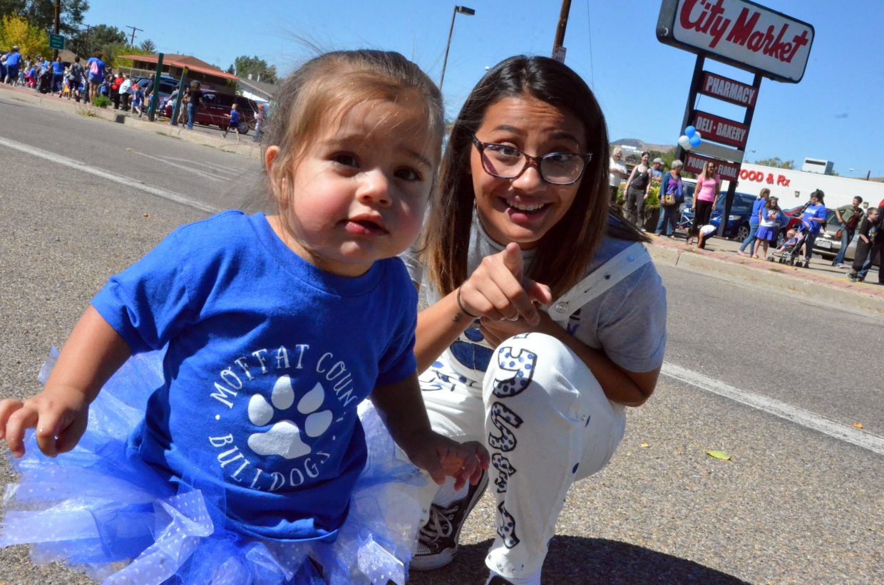 Moffat County High School's Alyssa Chavez attempts to get young football fan Teddi DiGrigoli's attention during Friday's Homecoming parade.