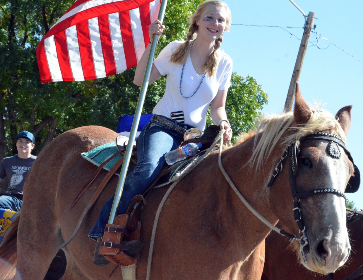 Moffat County High School's Brianna Burkett hoists the American flag on horseback during the Homecoming parade in September 2018.