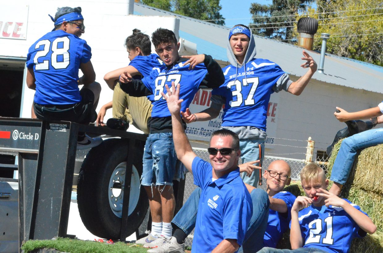 Moffat County High School football coaches and players greet spectators during the Homecoming parade Friday.