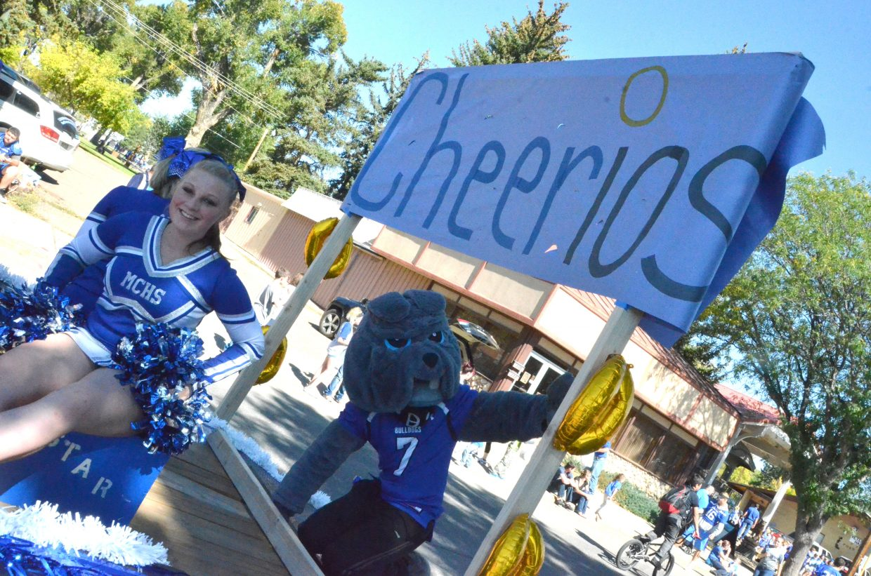 The Moffat County High School cheerleaders and mascot wave from the Cheerios float during the Homecoming parade Friday.