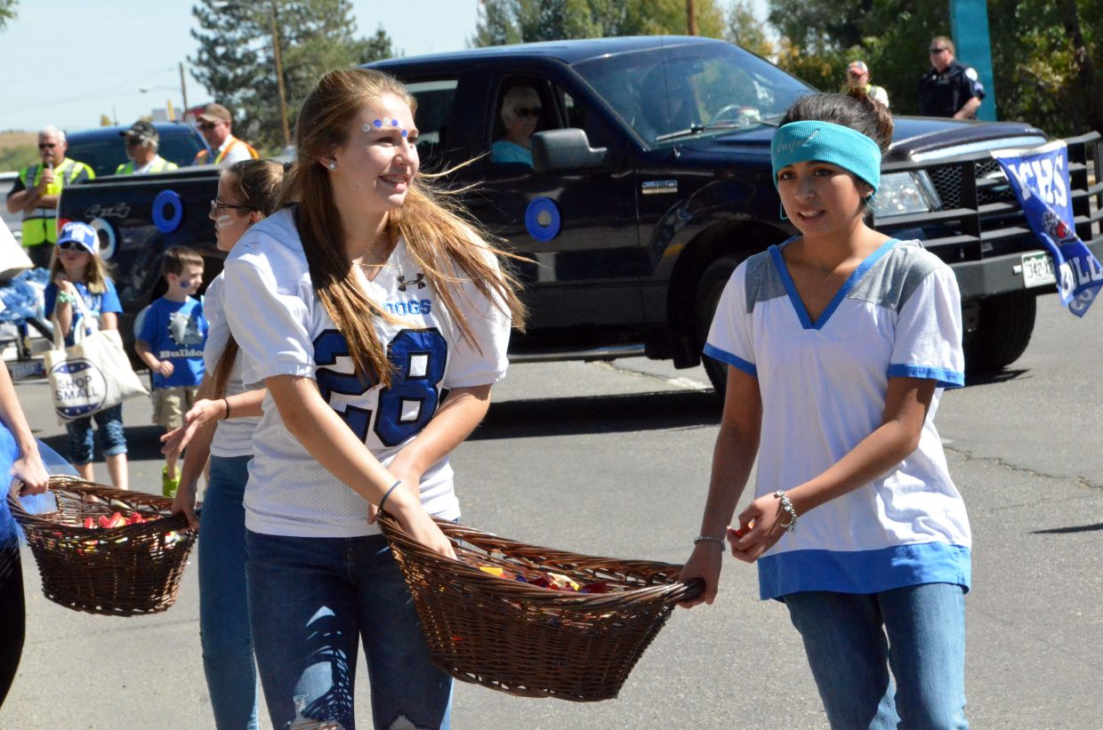 Moffat County High School students haul baskets of candy to hand out during the Homecoming parade Friday.