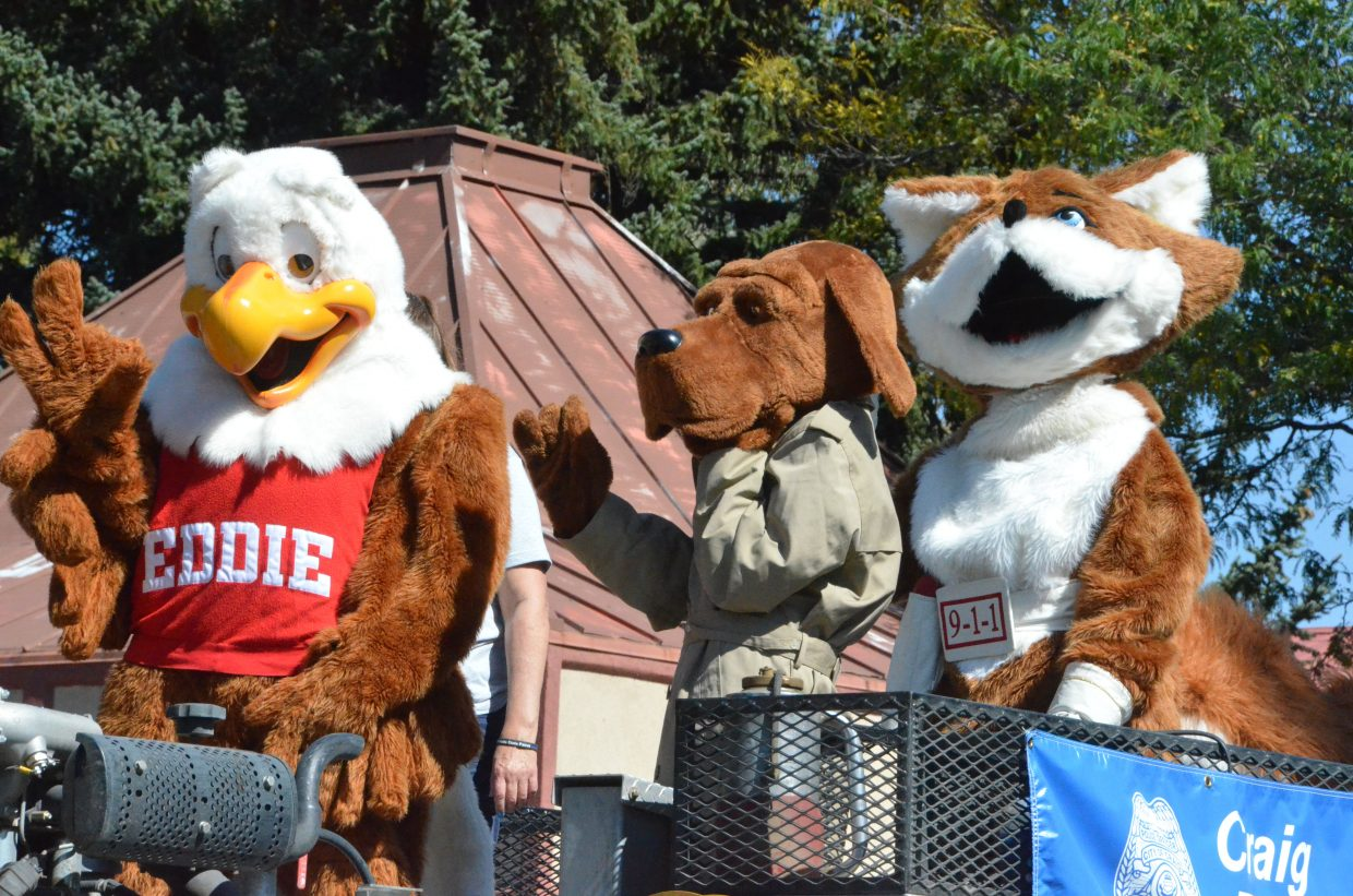 Safety mascots Eddie Eagle, McGruff the Crime Dog and Red E. Fox greet spectators during the Moffat County High School Homecoming parade Friday.