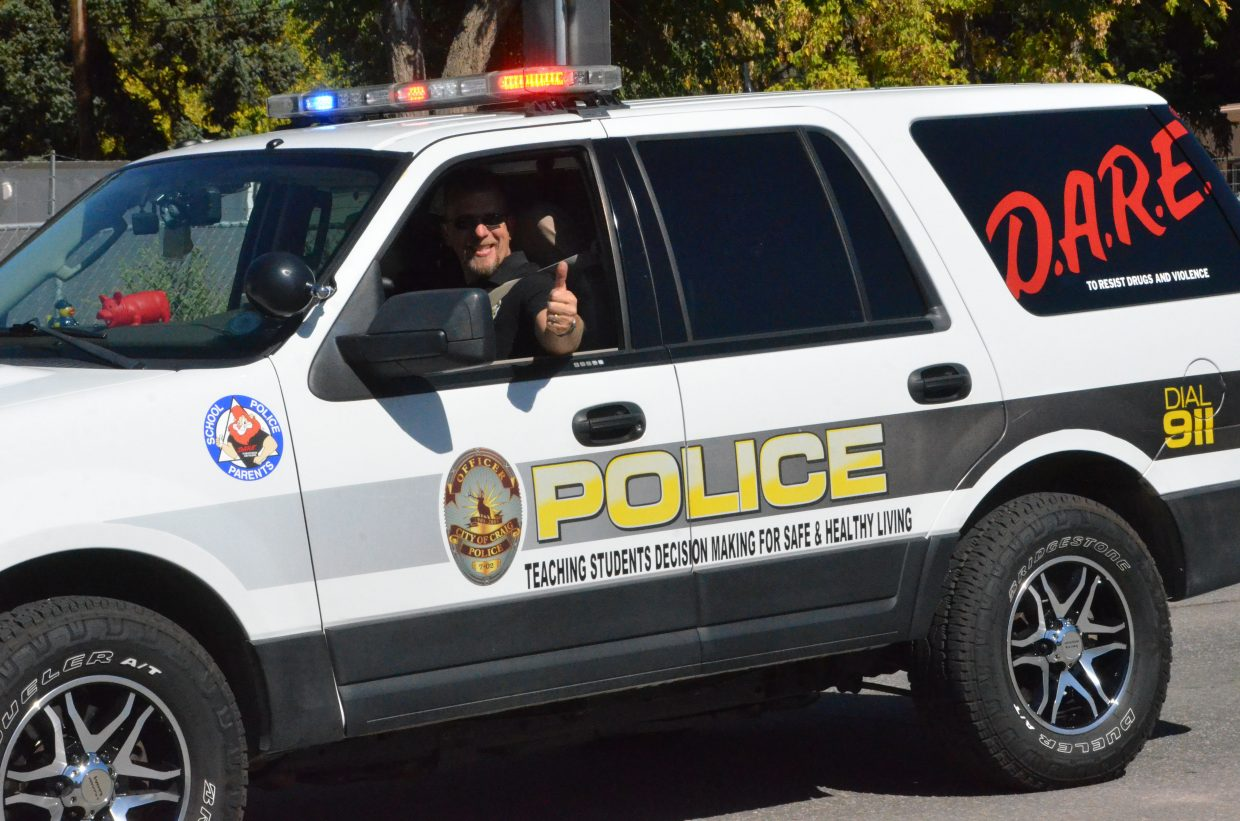 Craig Police Department's Ryan Fritz flashes a thumbs-up during the Moffat County High School Homecoming parade Friday.