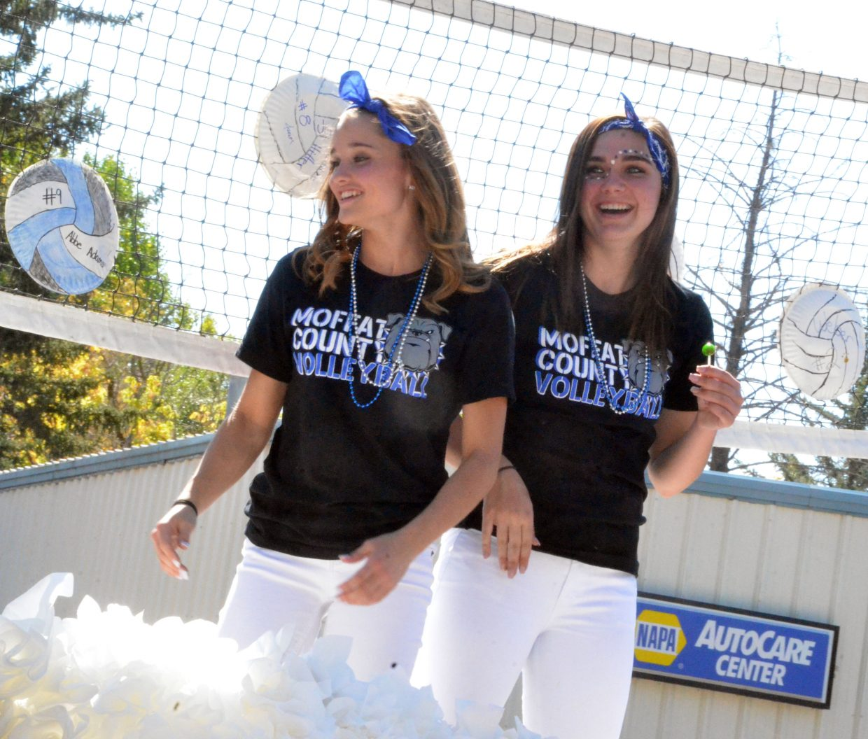 Bulldog volleyball players Stephenie Swindler and Jenna Timmer share a laugh on a float in the Moffat County High School Homecoming parade Friday.