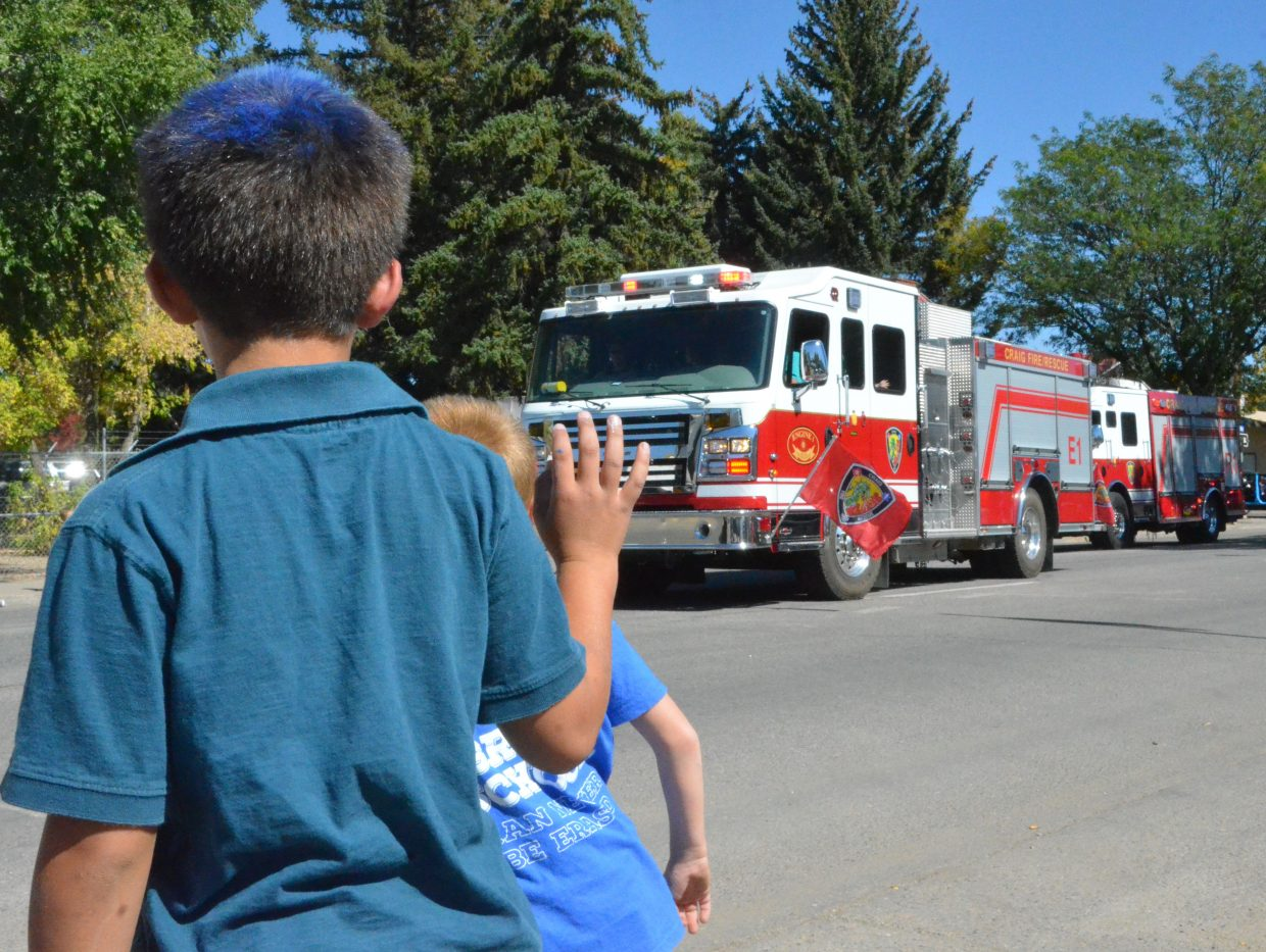 Young spectators wave to firefighters in the Moffat County High School Homecoming parade Friday.