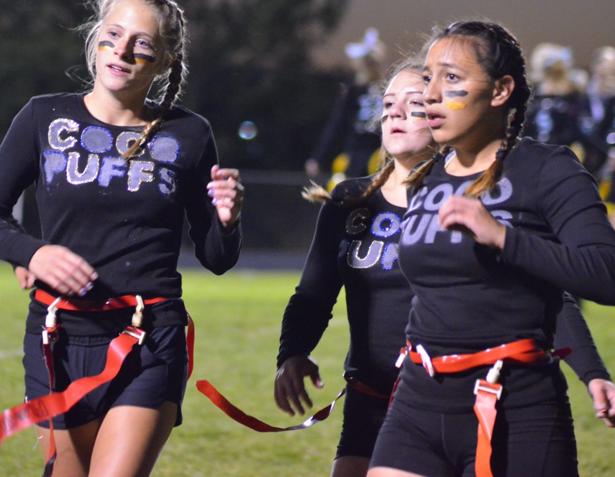 Members of Coco Puffs come off the field for a huddle during Moffat County High School's Monday Powder Puff Football.