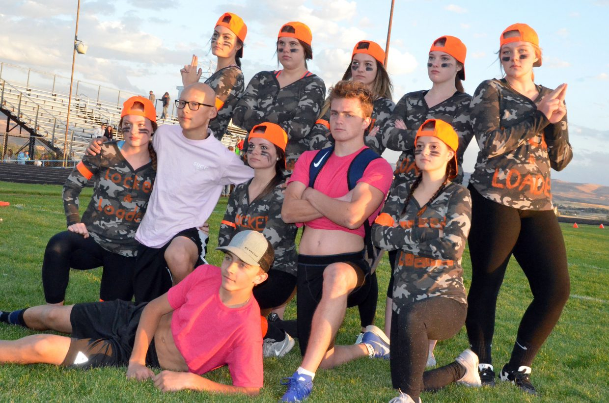 The members of Locked & Loaded gather on the field before Moffat County High School's Monday Powder Puff Football.