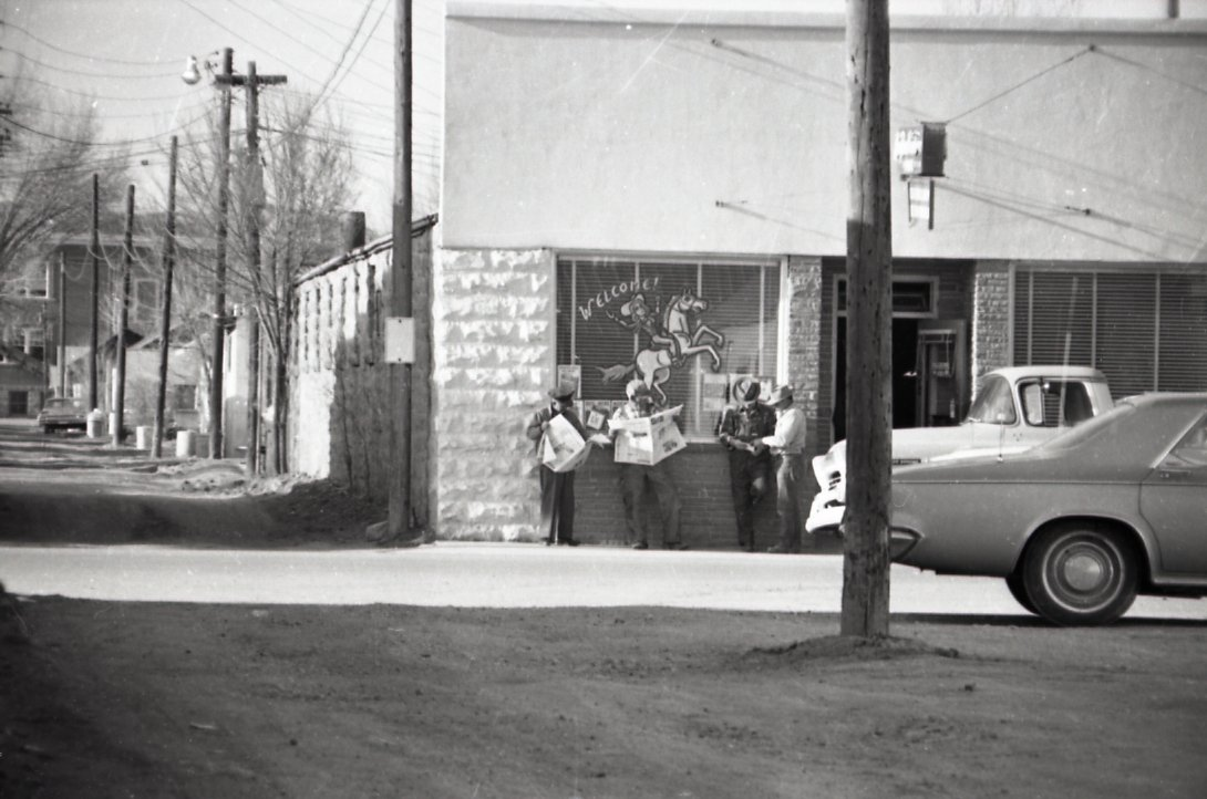Unidentified men stand in front of Galveston Bar, circa 1963. The building became the location of a mercantile and is now the home of Draper Insurance.
