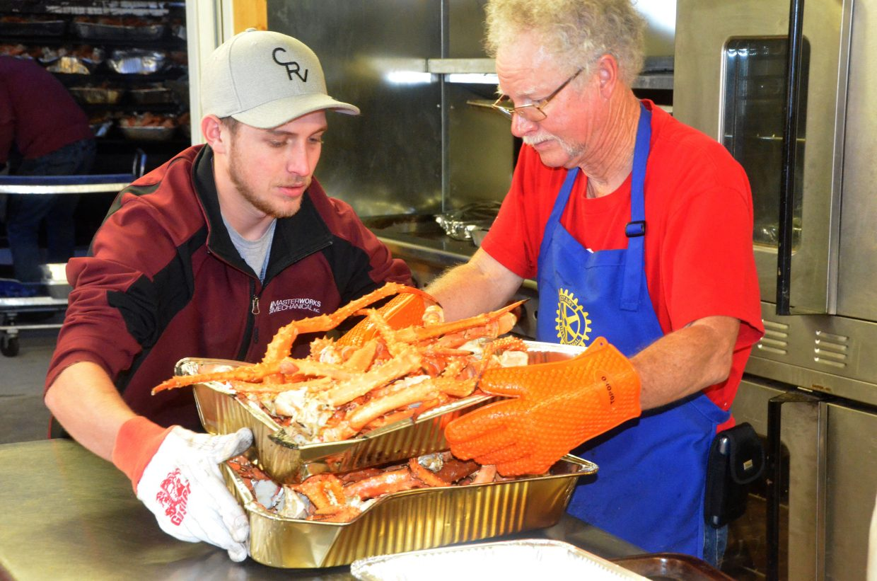 Volunteers bring freshly-cooked king crab through the Moffat County Fairgrounds Pavilion kitchen at Craig Chamber of Commerce Crabfest.