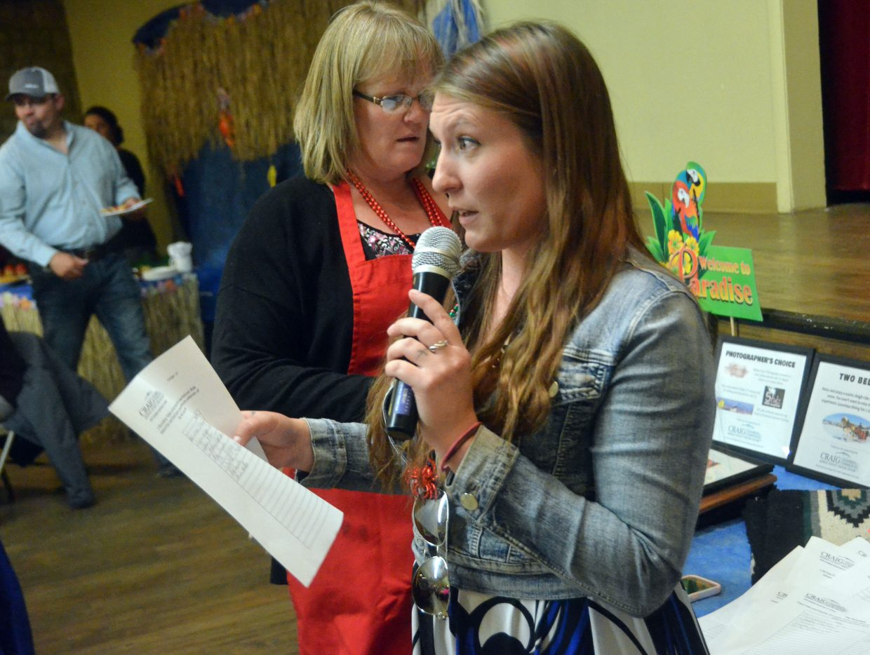 Kaitlyn Marchbanks announces winning bids following the silent auction at Craig Chamber of Commerce Crabfest.