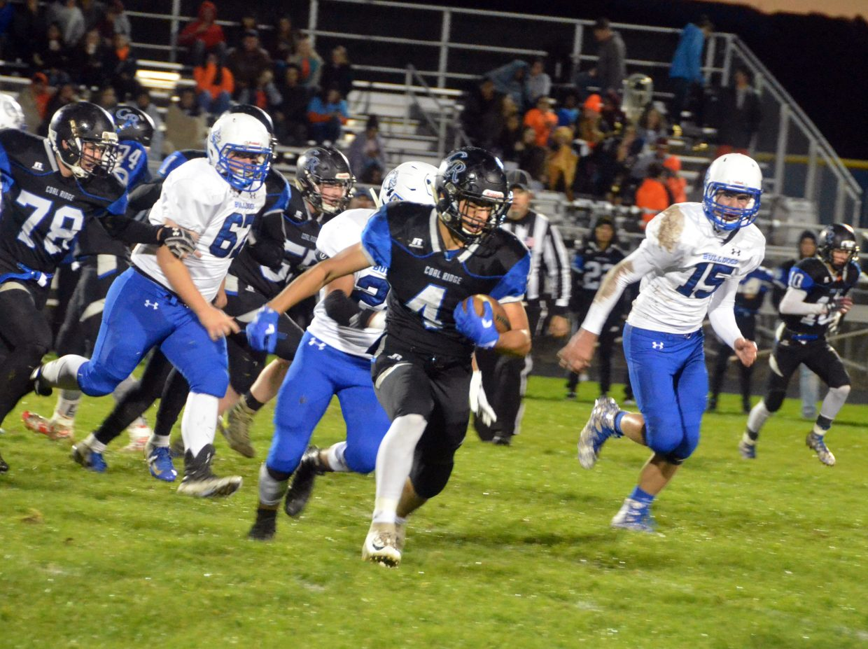 Moffat County High School defenders pursue Coal Ridge running back Adrian Garcia.