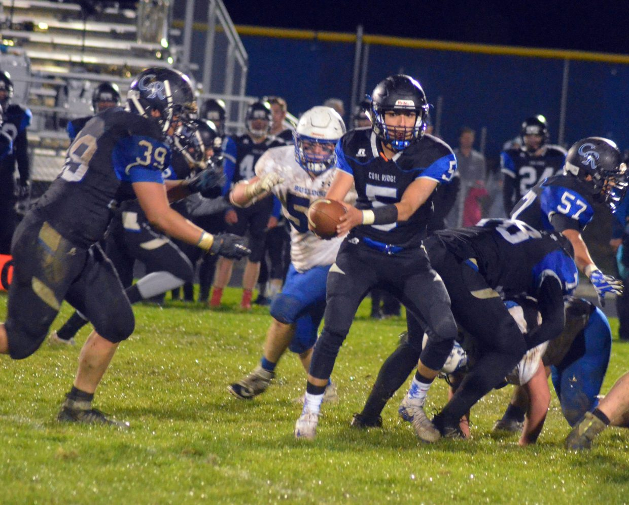 Moffat County High School's Jared Baker comes around the corner as Coal Ridge quarterback Oscar Salazar hands off to Damian Spell.