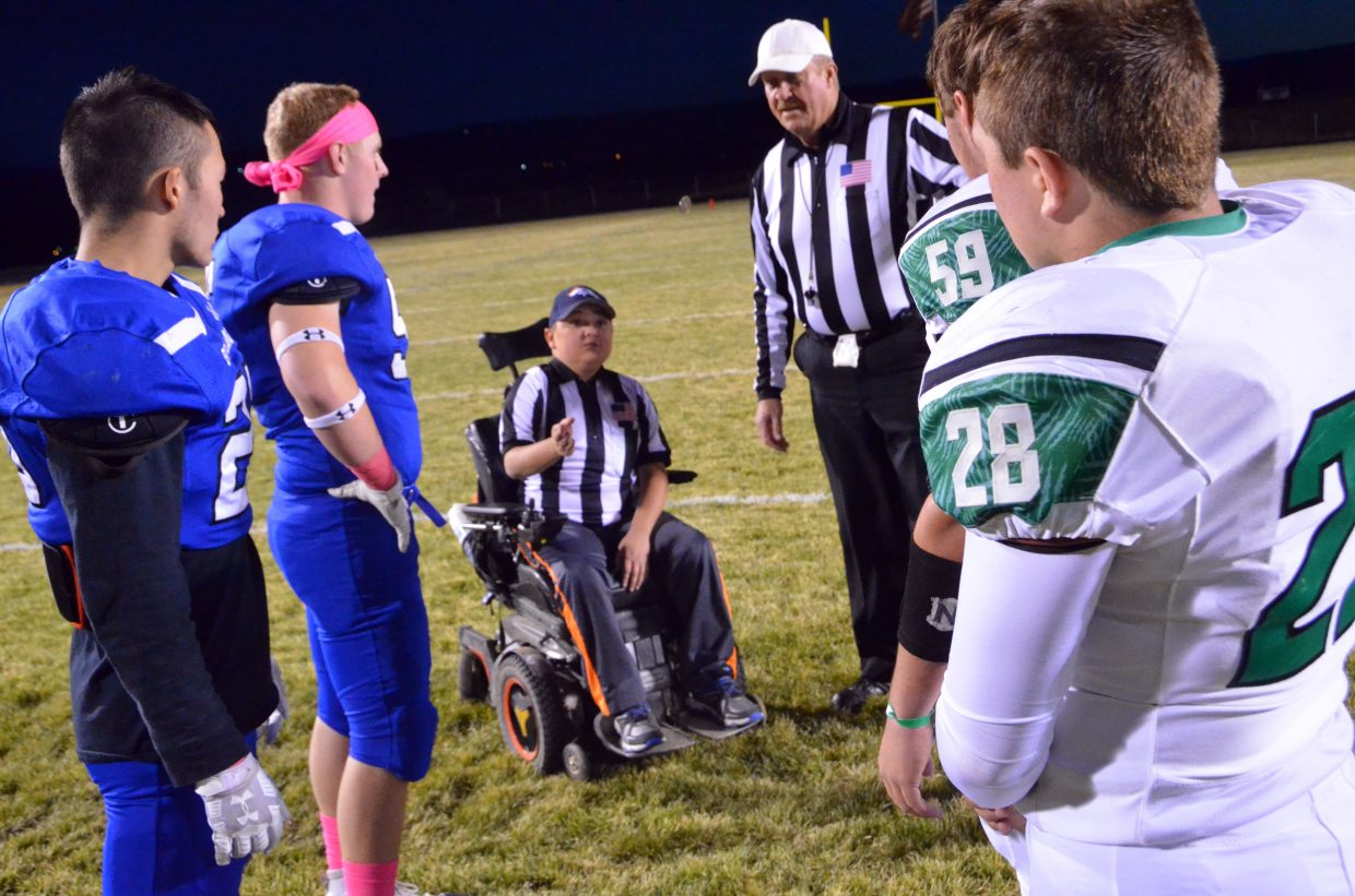 Honorary referee JP Price performs the coin toss to start the game between Moffat County High School and Delta.