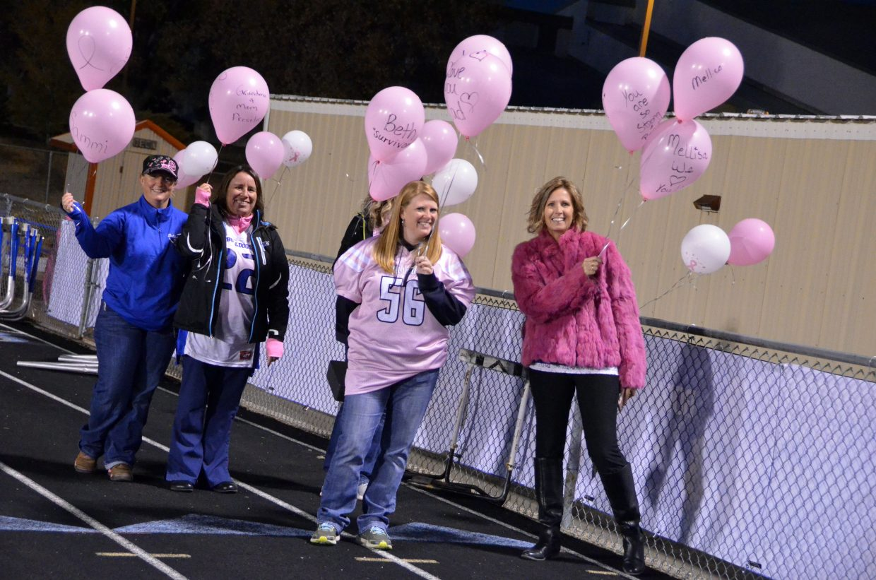 Moffat County High School football parents wait to release pink balloons in honor of cancer survivors before kickoff.