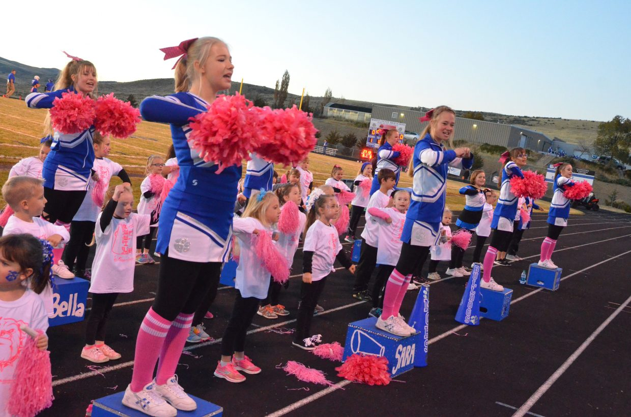 Members of the Junior Bulldog Fall Cheer Clinic join the Moffat County High School spirit team in pre-game warmups.