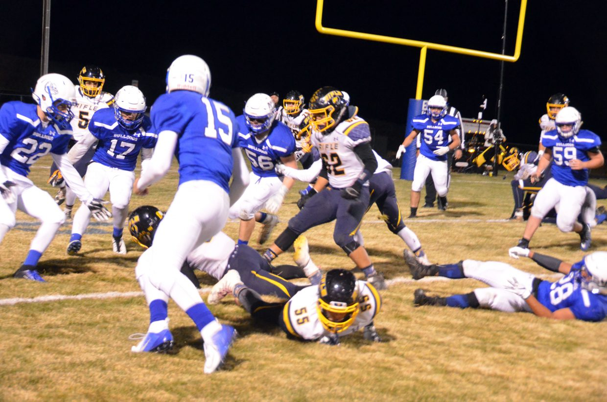 Moffat County High School defenders swarm Rifle's Levi Warfel as he dives for extra yardage.