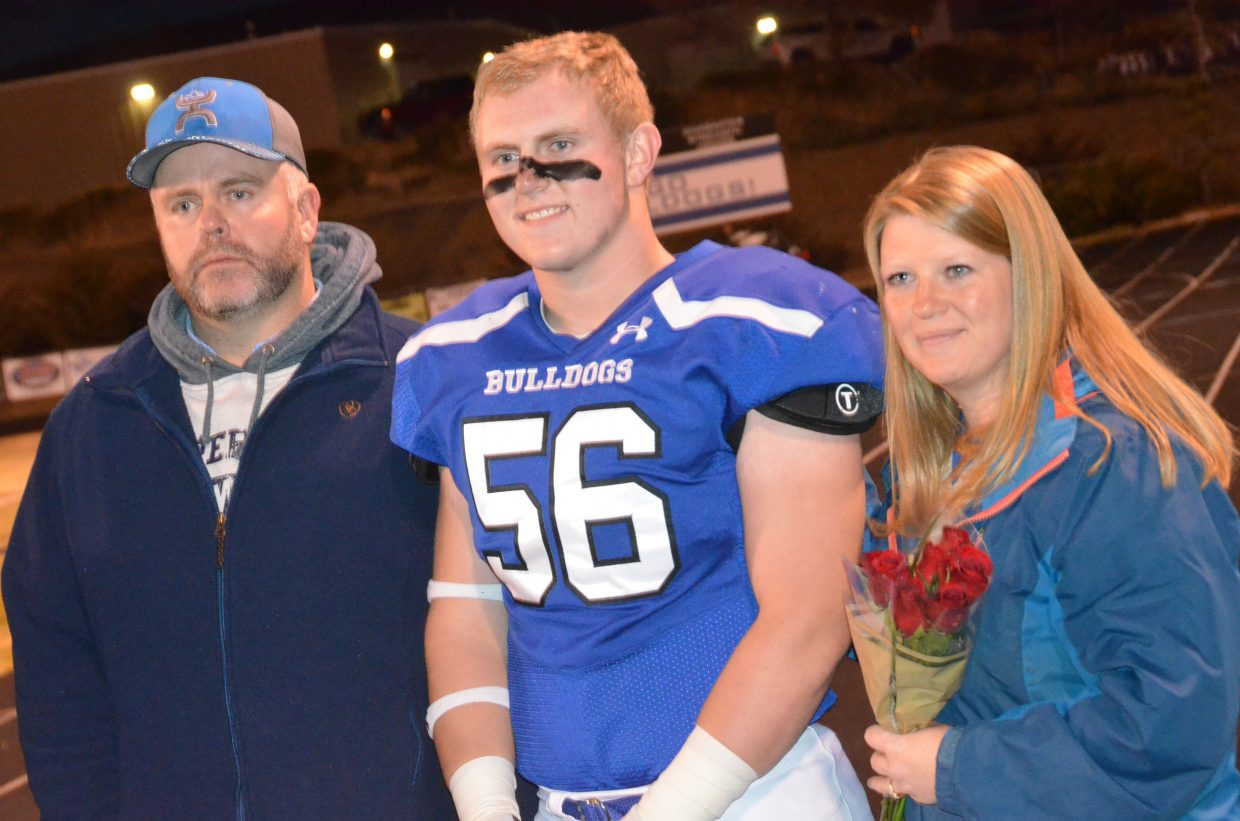 Moffat County High School's Jared Baker is joined by parents as part of Senior Night.
