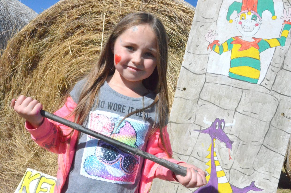 Zariah Stover, 7, displays the needle in a haystack found at the hay maze during  Wyman Living History Museum's pumpkin patch.