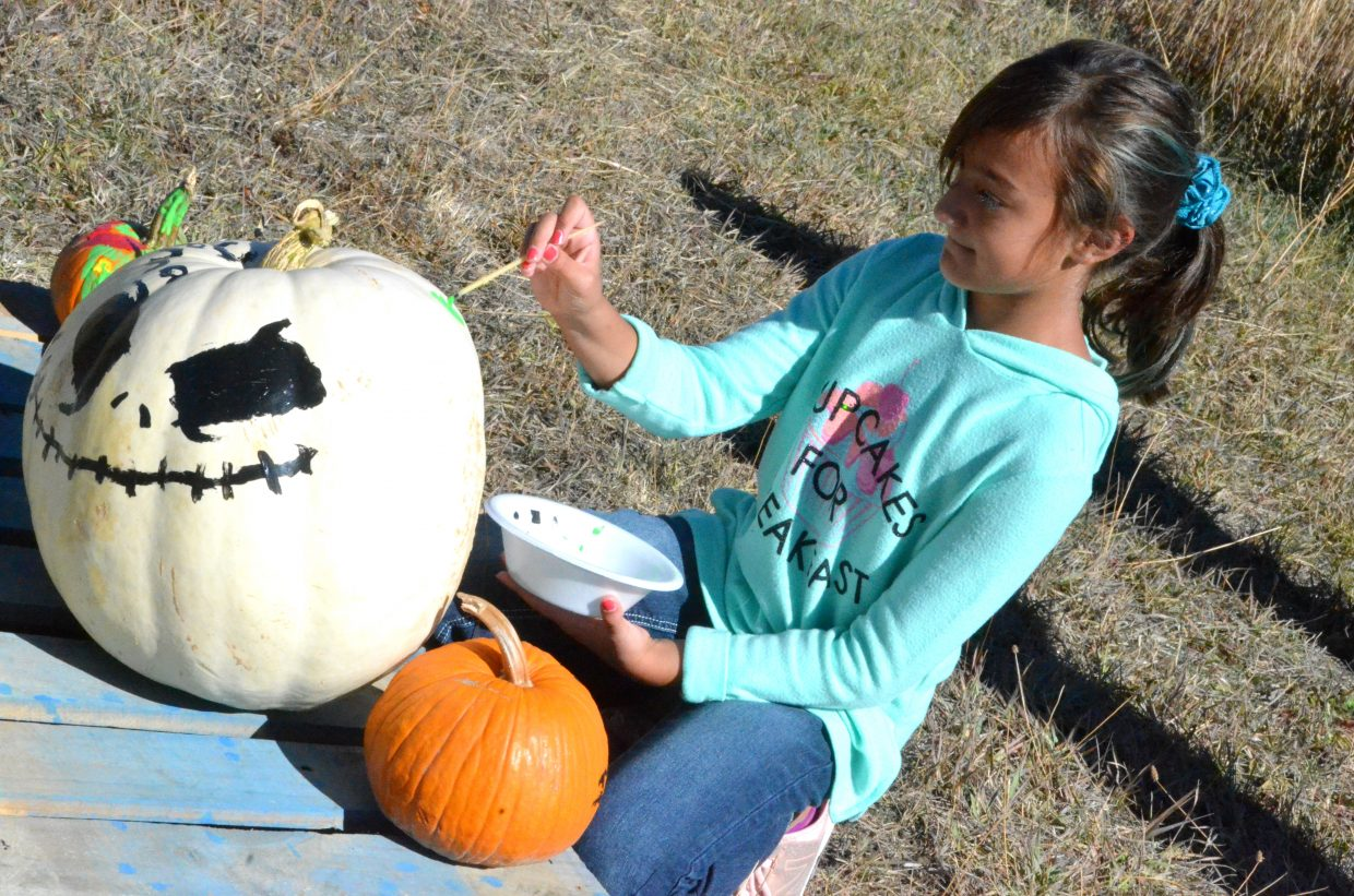 Jenna Hyer, 9, puts the finishing touches on Jack Skellington's likeness at Saturday's pumpkin patch at Wyman Living History Museum.