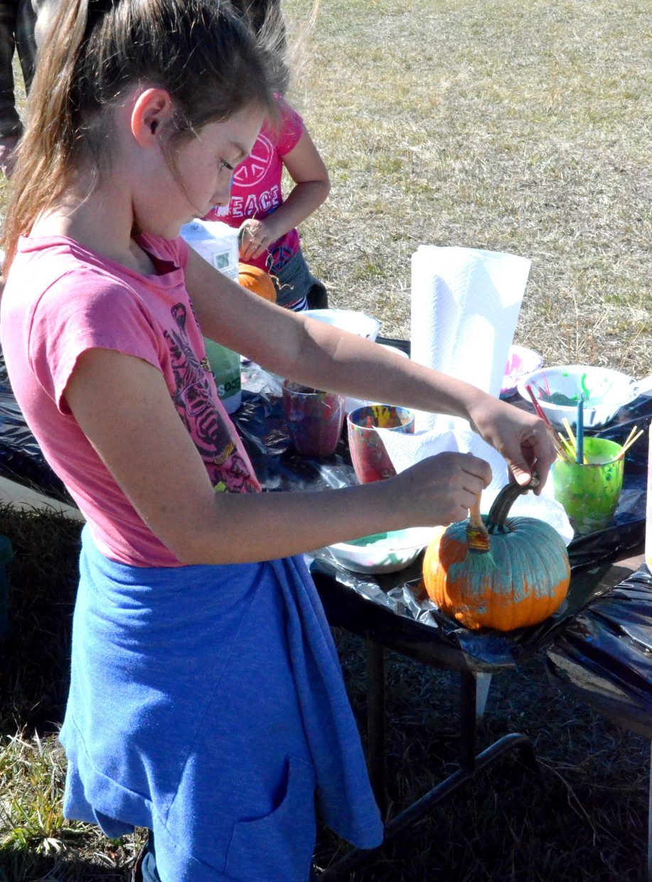 Marilee Mowdy, 9, loads up on the green at the painting station at Saturday's pumpkin patch at Wyman Living History Museum.