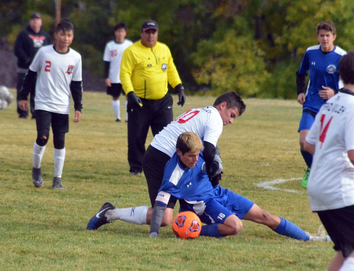 Moffat County High School's Pedro Romero does everything he can — including abosrbing a foul from his opponent — to get the ball back from Grand Valley.