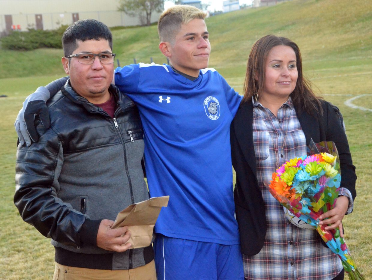 Moffat County High School's Pedro Romero gathers with family during a halftime ceremony for Senior Night for MCHS boys soccer.