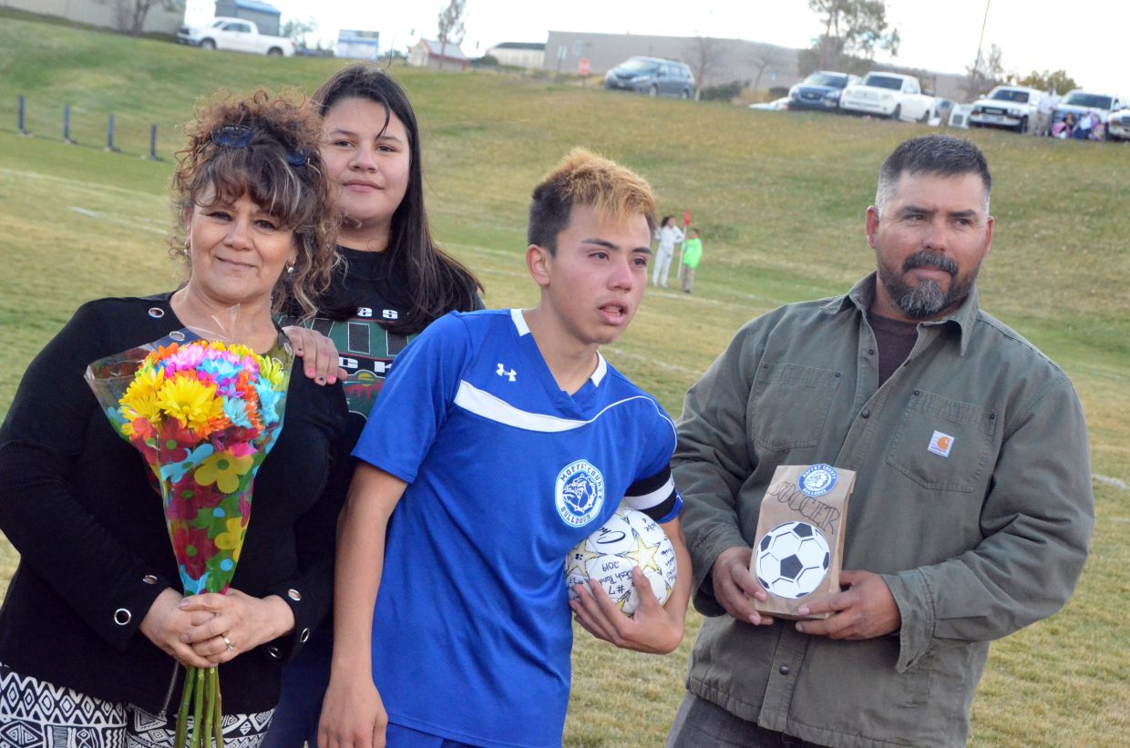 Moffat County High School's Josh Pando gathers with family during a halftime ceremony for Senior Night for MCHS boys soccer.
