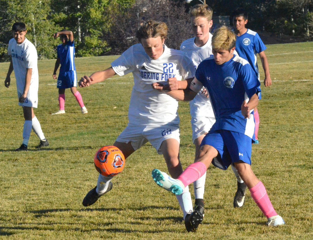 Moffat County High School's Pedro Romero knocks away the ball from Roaring Fork opponents.