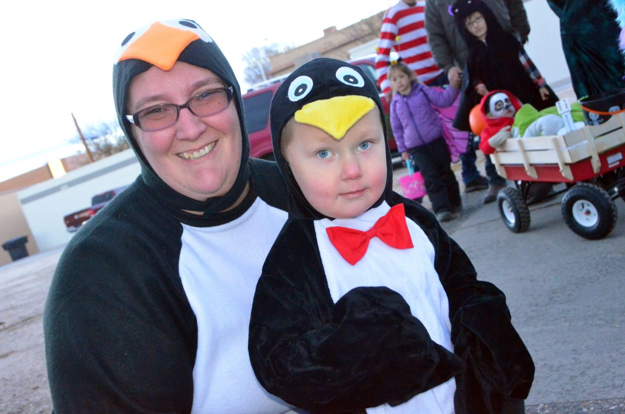 Brandi and Alaric Miller, 3, dress as mother and child penguins Wednesday during Trick or Treat Street along Yampa Avenue and Victory Way.