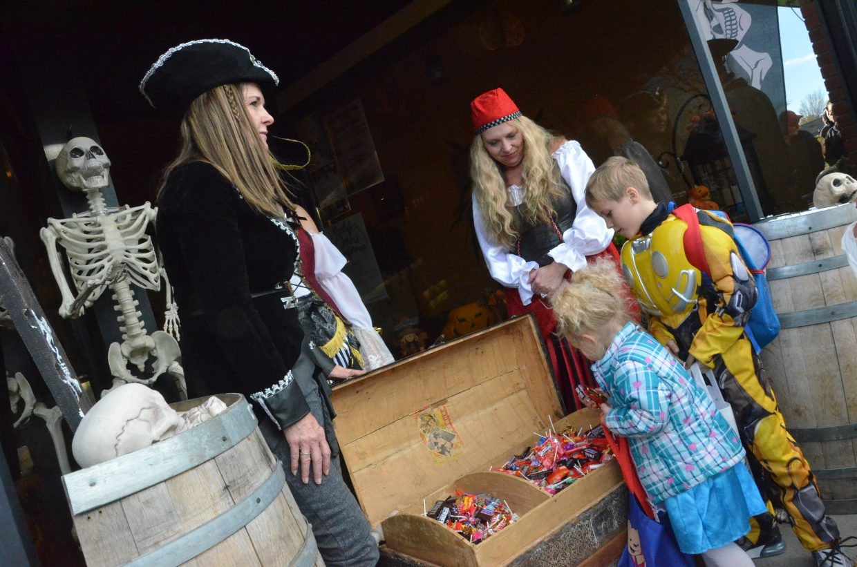 Kids have their pick of candy from a treasure chest at Flint Personnel Wednesday during Trick or Treat Street along Yampa Avenue and Victory Way.