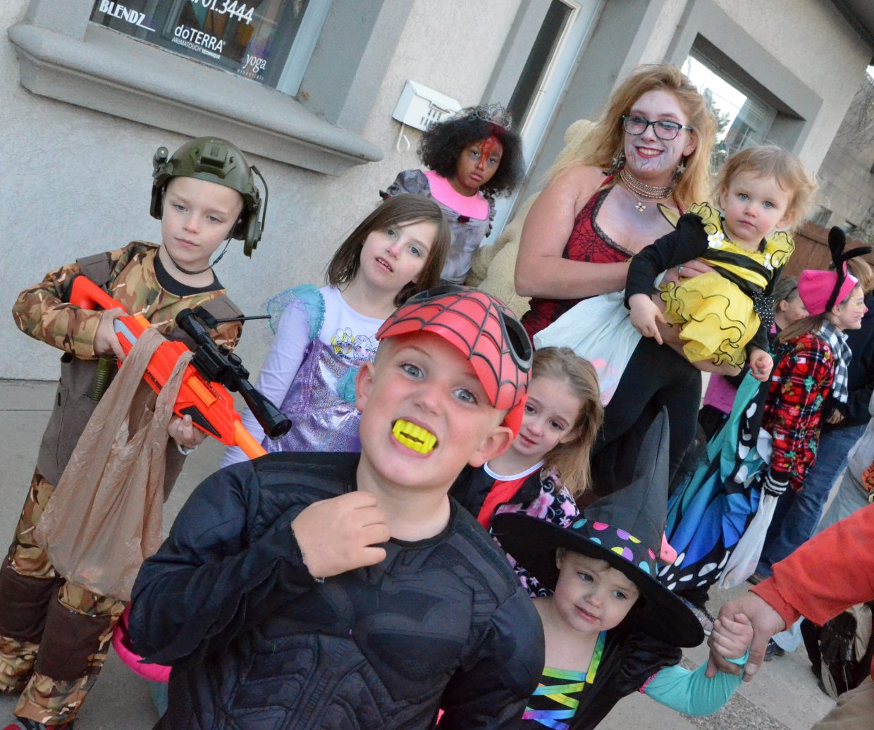 A cluster of trick-or-treaters grab a photo during the 2018 Trick or Treat Street along Yampa Avenue and Victory Way.