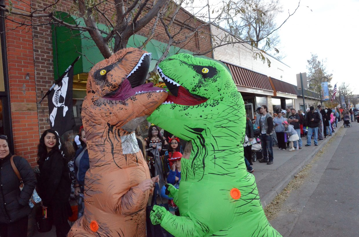 A pair of T-Rexes battle for dominance Wednesday during Trick or Treat Street along Yampa Avenue and Victory Way.