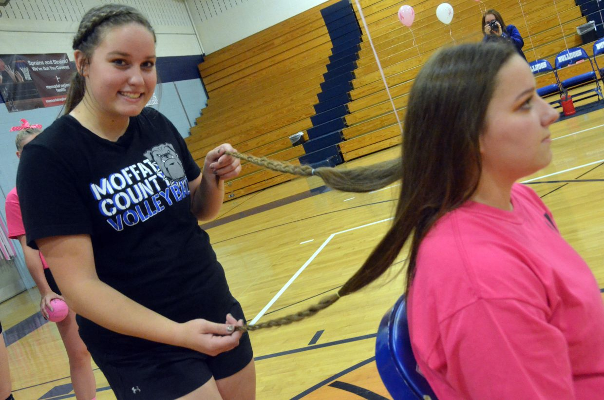 Moffat County High School's Taytum Smercina, left, displays the full length of older sister Ebawnee's hair before she gets it cut for a donation to Wigs for Kids.