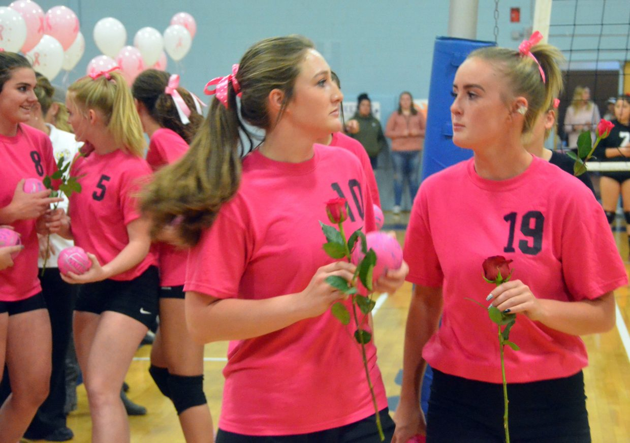 Moffat County High School's Tiffany Hildebrandt and Bailey Lawton and teammates prepare to hand out roses to honor cancer survivors at MCHS's Pink Night.