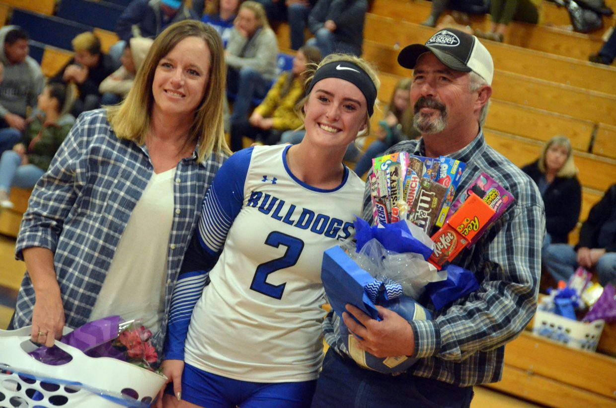 Moffat County High School's Bailey Lawton is joined by her parents on the court during the Senior Night ceremony.