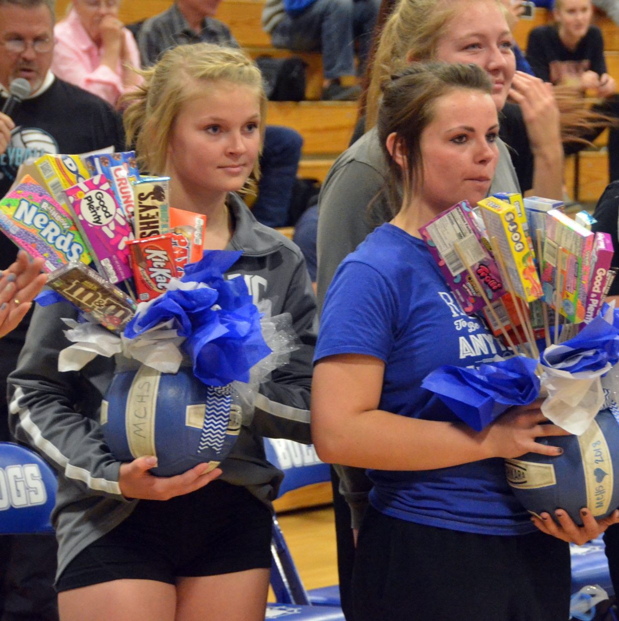 Moffat County High School JV volleyball players Jacie Evenson, left, and Darbi Zimmerman wait to present gift baskets for upperclassmen during Senior Night.