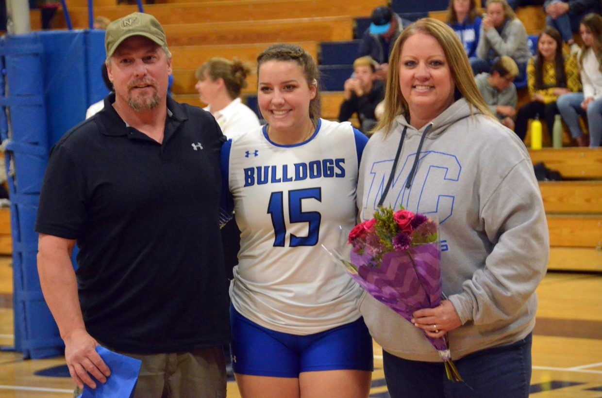 Moffat County High School's Ebawnee Smercina is joined by her parents on the court during the Senior Night ceremony.