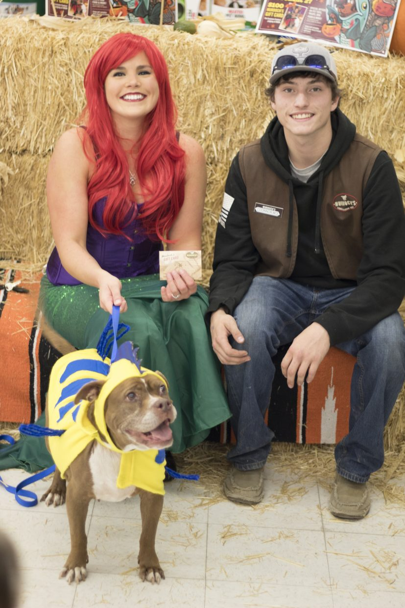 Alisa Brown and her canine friend, Brown Bear, receive a $100 Murdoch's gift card from Murdoch's employee Connor Murphy after being named winners of the business's annual Growl-O-Ween event.