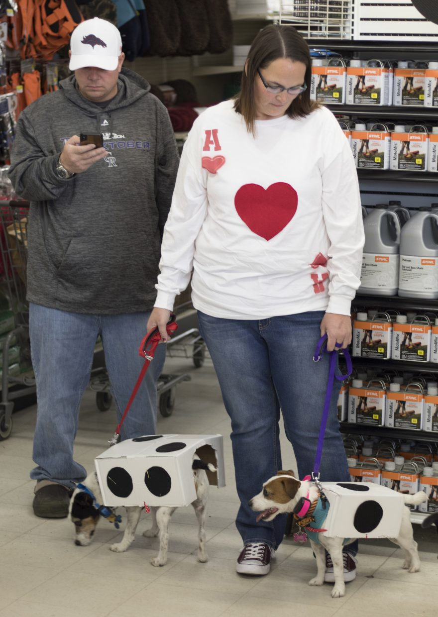 Jeff and Morgan Gruebel and their dogs Gunner and Sophie await the announcement of the winner of Murdoch's annual Growl-O-Ween costume contest on Saturday.