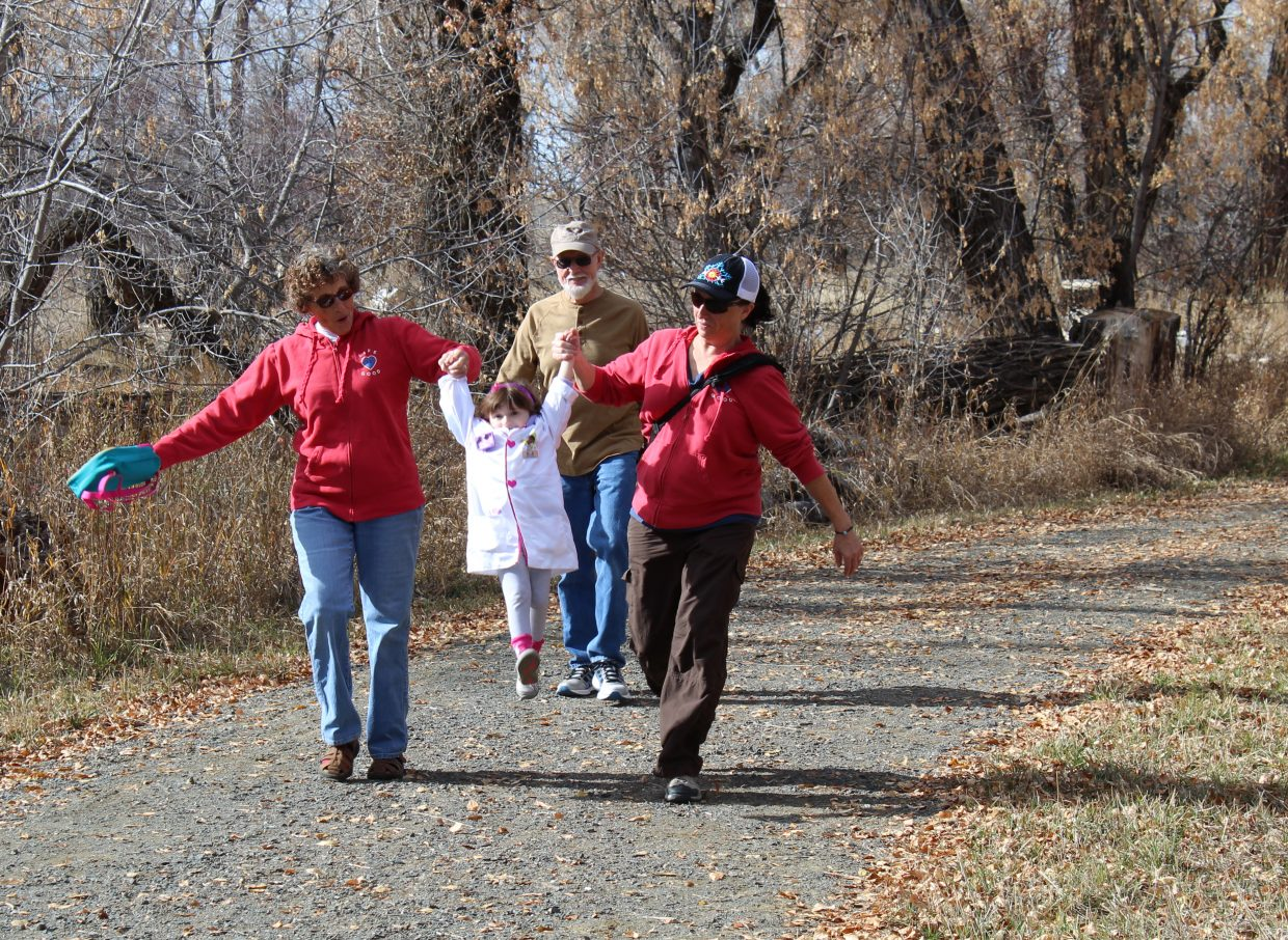 Jeannie Albee and Jen Bergstrom give Aly Bergstrom a quick lift while walking the trail during Saturday's Hike or Treat event at Yampa River State Park.