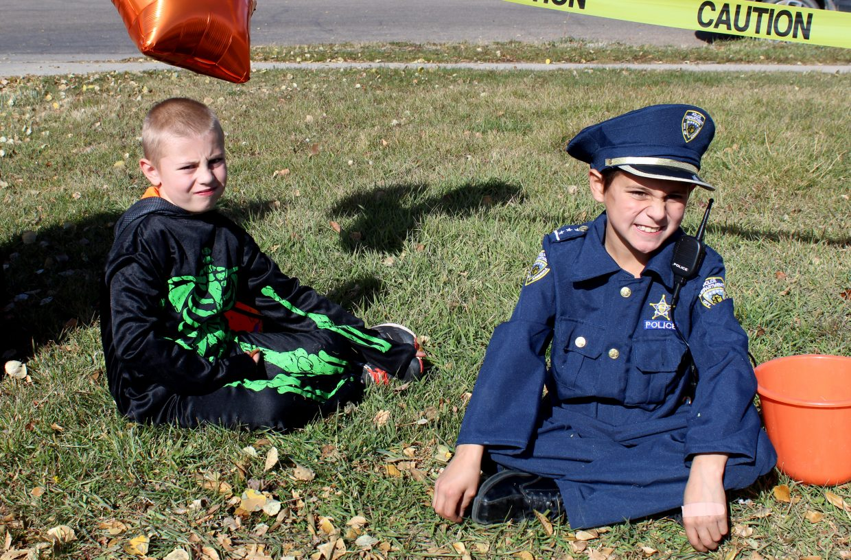 Aiden Antonacci, 7, left, and Zander Martinez, 9, take a break from gathering candy Saturday to enjoy some of their spoils during a Trunk or Treat event at Thunder Rolls Bowling Center.