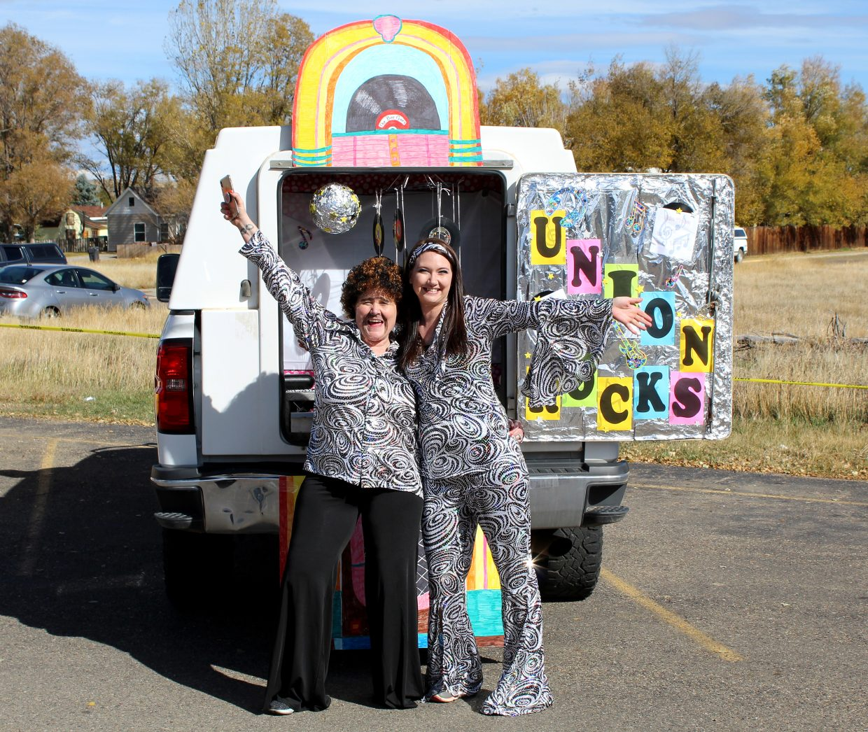 RaChell Dschaak, left, and Whitney Sadvar show off their '70s style while passing out treats to local kids Saturday at Thunder Rolls Bowling Center.