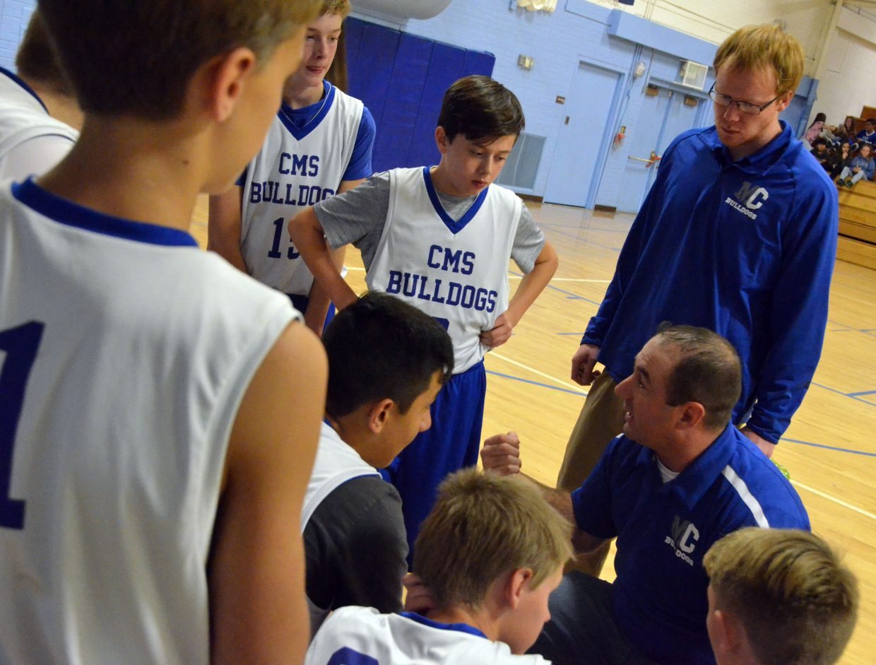 Craig Middle School basketball players gather around coach Mark Carlson at halftime against Meeker.
