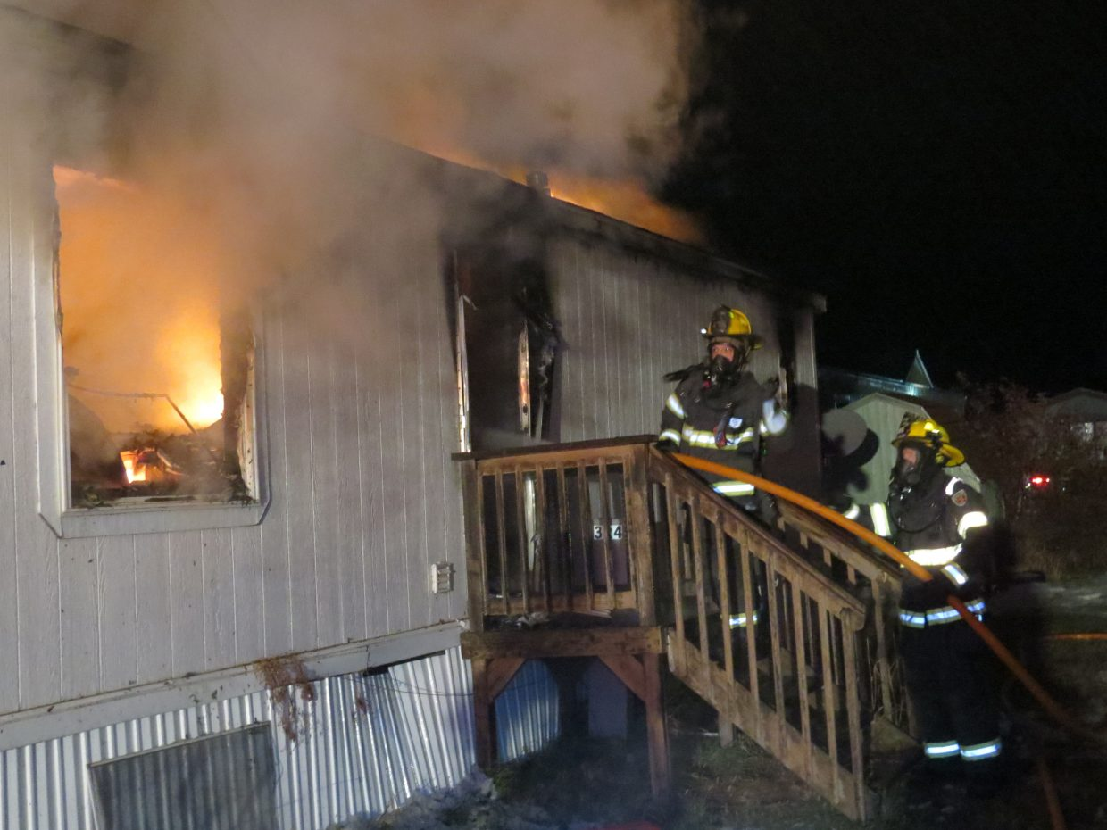 Members of Craig Fire/Rescue enter a burning home at Cedar Mountain Trailer Park early Friday morning.