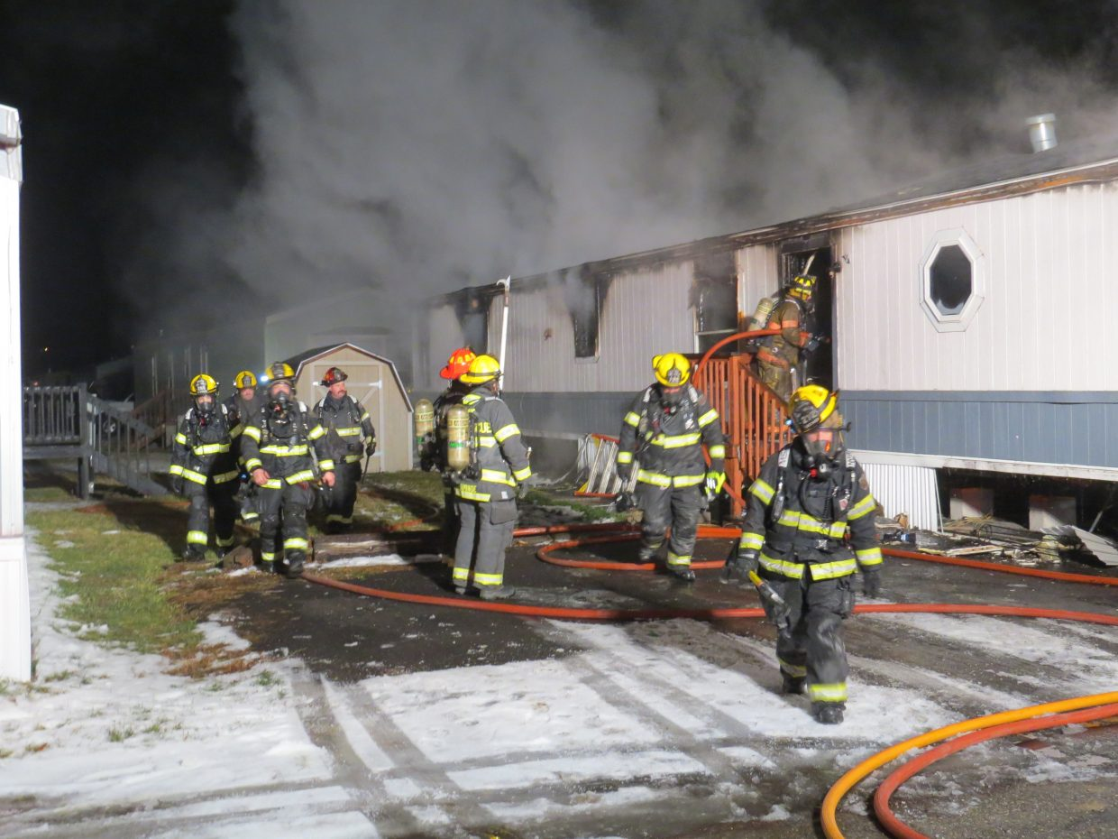 Craig Fire/Rescue extinguishes the flames of a home at Cedar Mountain Trailer Park early Friday morning.