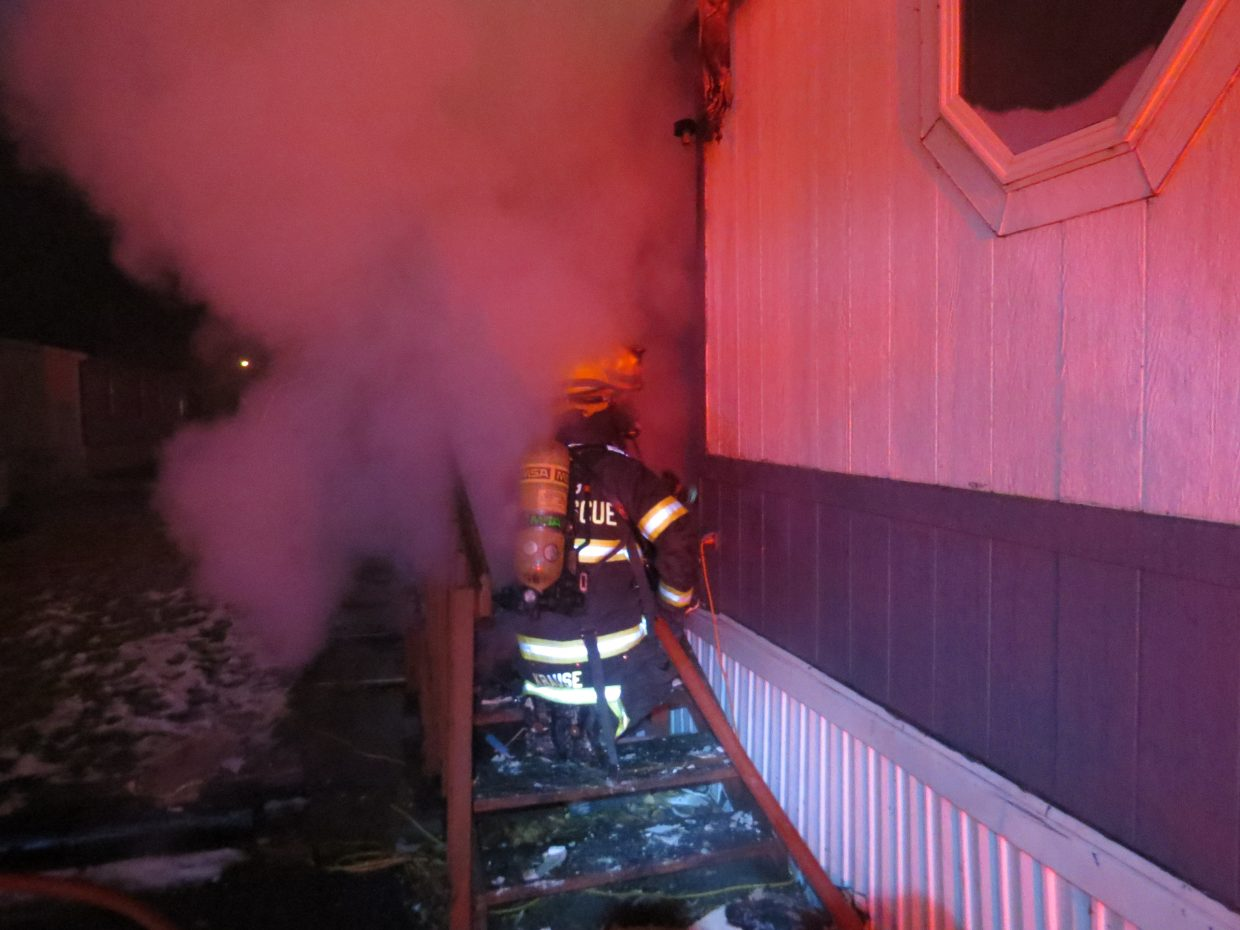 Craig Fire/Rescue members enter a smoke-filled home at Cedar Mountain Trailer Park early Friday morning.