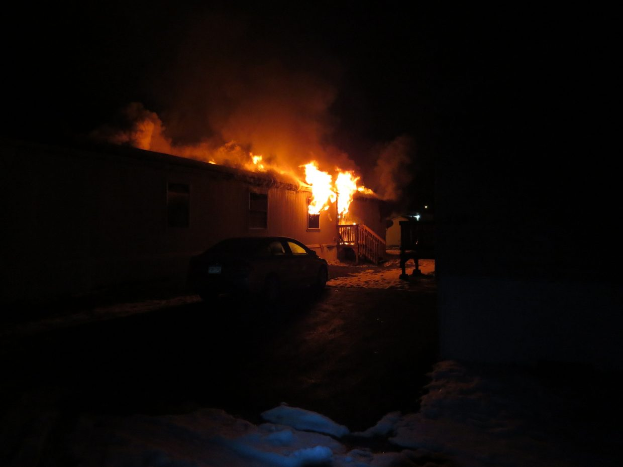 Flames erupt from a home at Cedar Mountain Trailer Park early Friday morning.