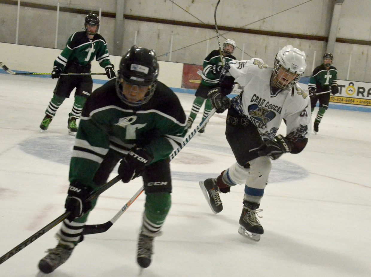 Tallyn Wagner goes after the puck near the boards during Craig Youth Hockey Association's 14U Bantam game against Telluride.